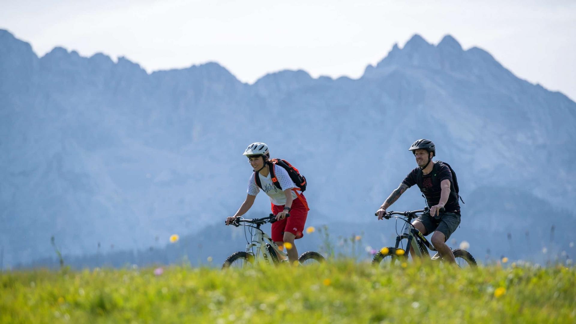 Paar mit E-Bikes vor Gebirge © GaPa Tourismus GmbH - Christian Stadler